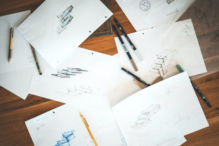 Scattered sheets of paper, each with a single sketch on it. The sketches are small, and look like they depict part of a staircase design.