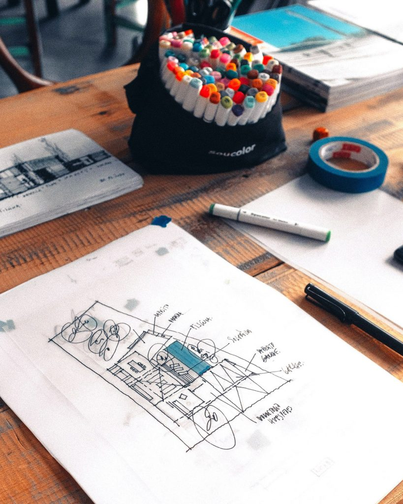 A sheet of paper depicting part of an architectural design that looks like a floor layout for a new building. The drawing is sitting on top of a worn wooden desk and there is a tub of coloured markers sitting being it.