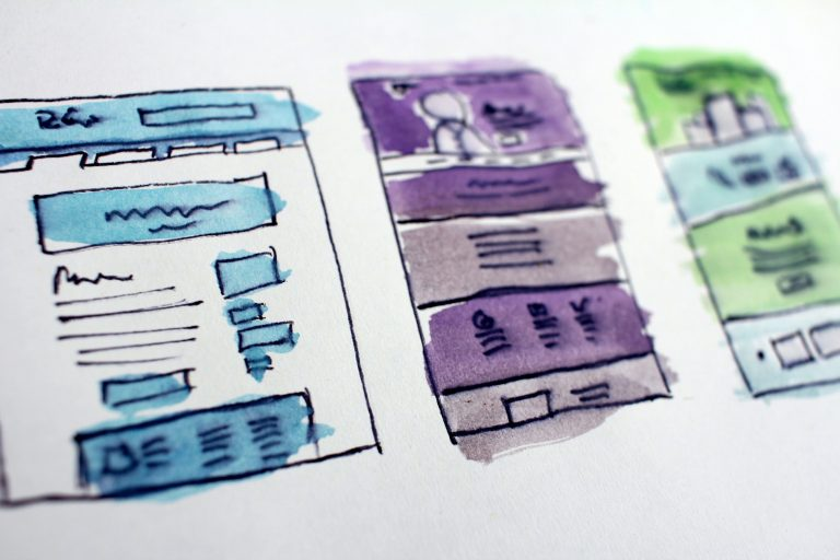 Sketched wireframes of a website design. THe wireframs have been painted blue, purple and green using vibrant watercolours.